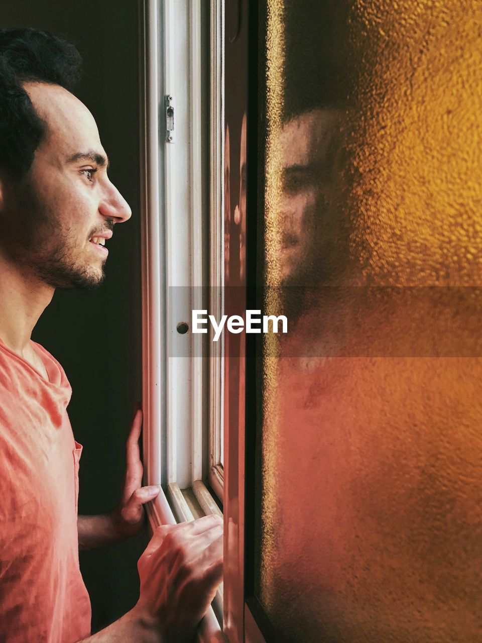 Profile View Of Man Looking Through Window At Home