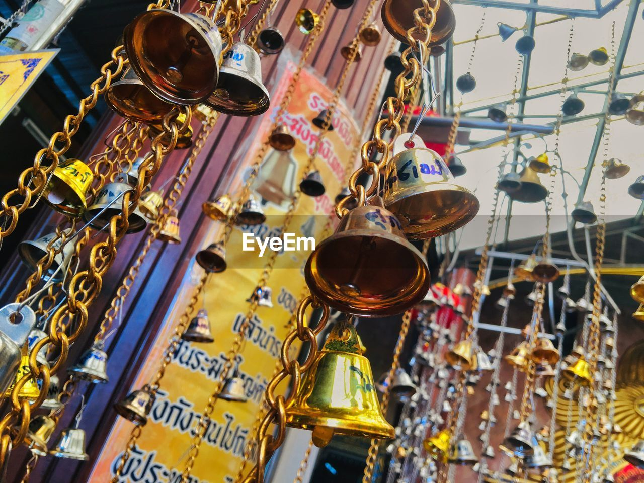 music, no people, hanging, musical instrument, indoors, low angle view, arts culture and entertainment, choice, variation, day, musical equipment, focus on foreground, gold colored, large group of objects, decoration, lighting equipment, still life, text, metal