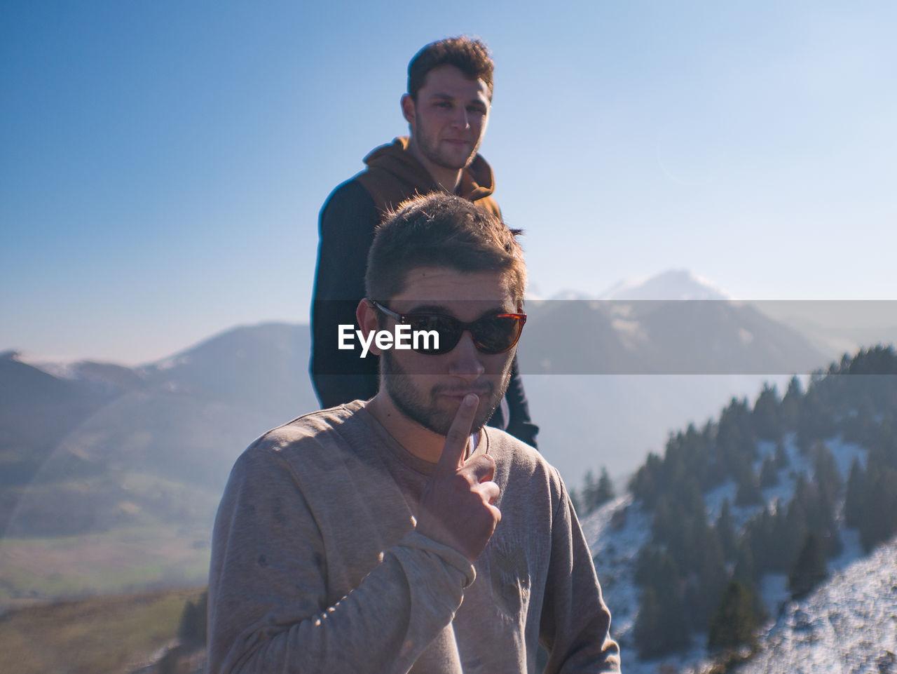 Portrait of friends on mountain against sky