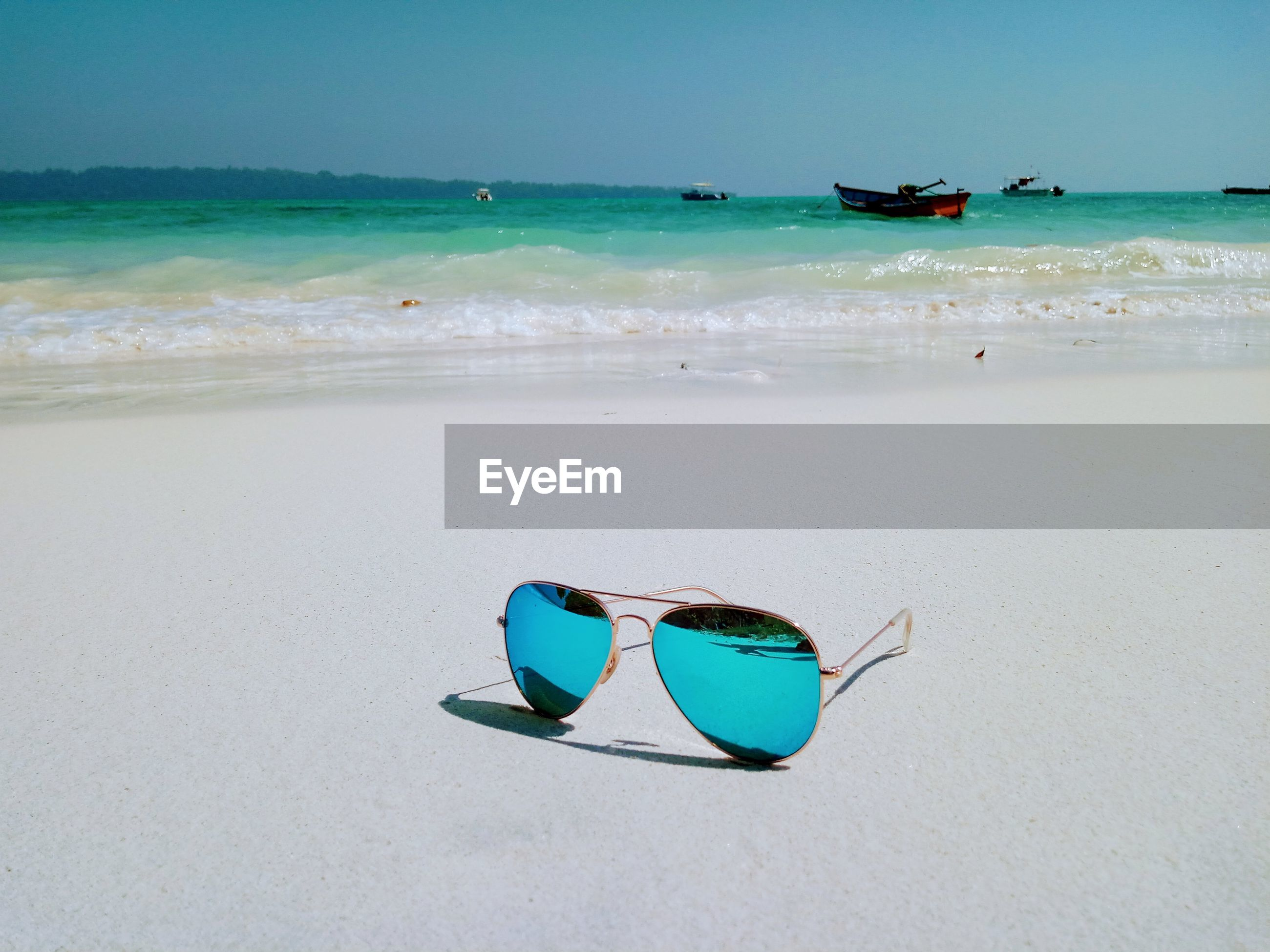 Ray ban sunglasses on beach against sky in havelock island