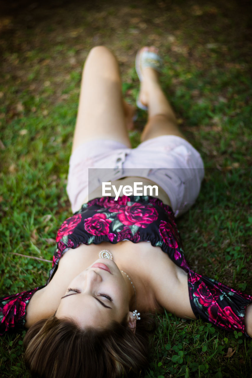High angle view of teenage girl lying on grassy field in park