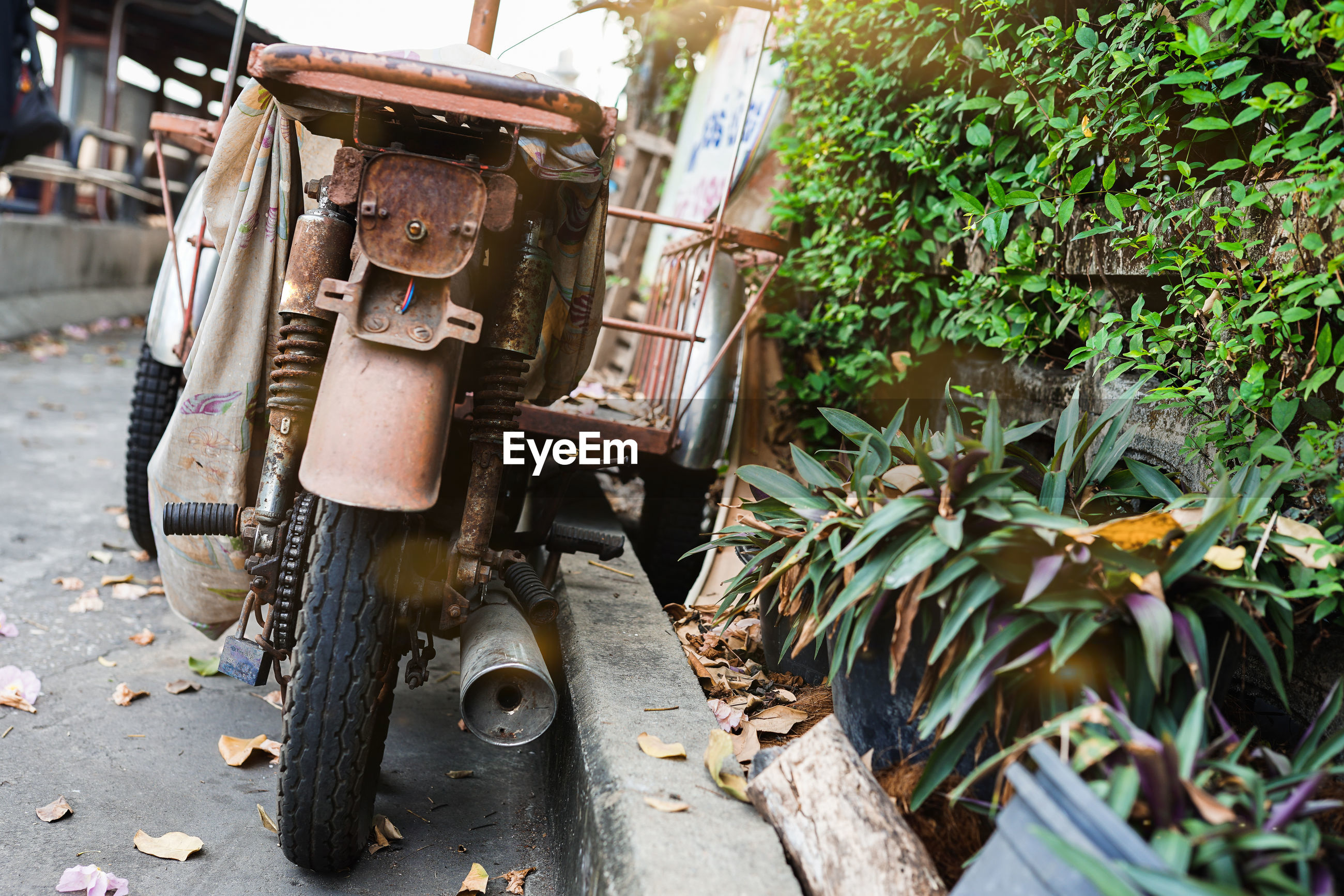The image of a rusty old motorcycle parked on the side of the road.