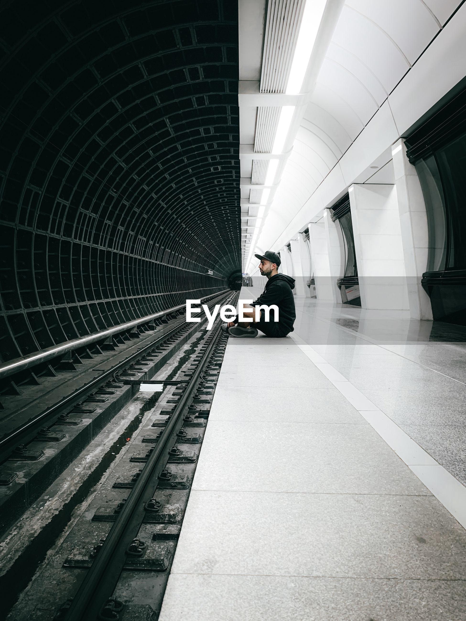 Man sitting at subway station platform