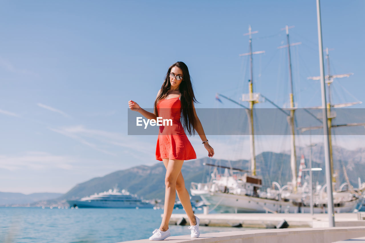 Full Length Portrait Of Young Woman On Promenade By Sea Against Sky