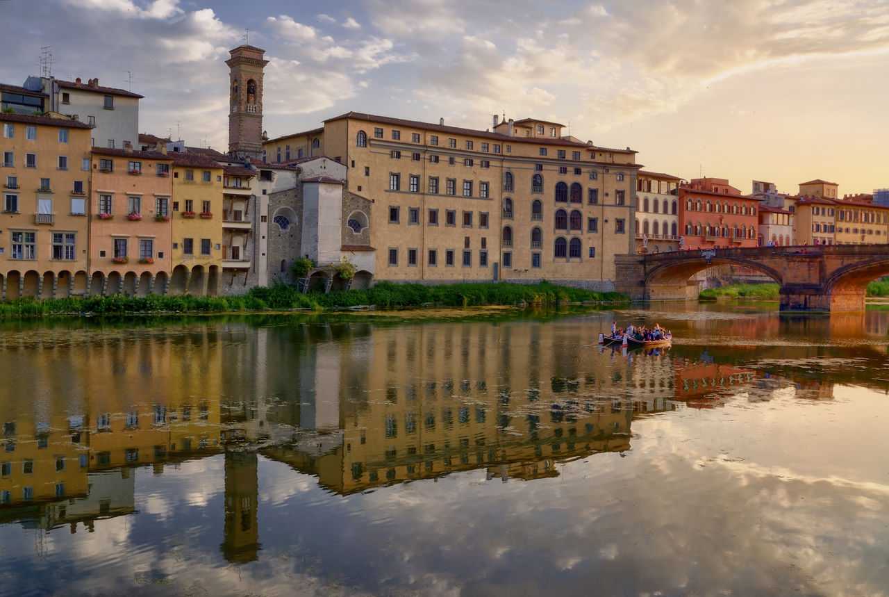 People Boating In Arno River Against Sky