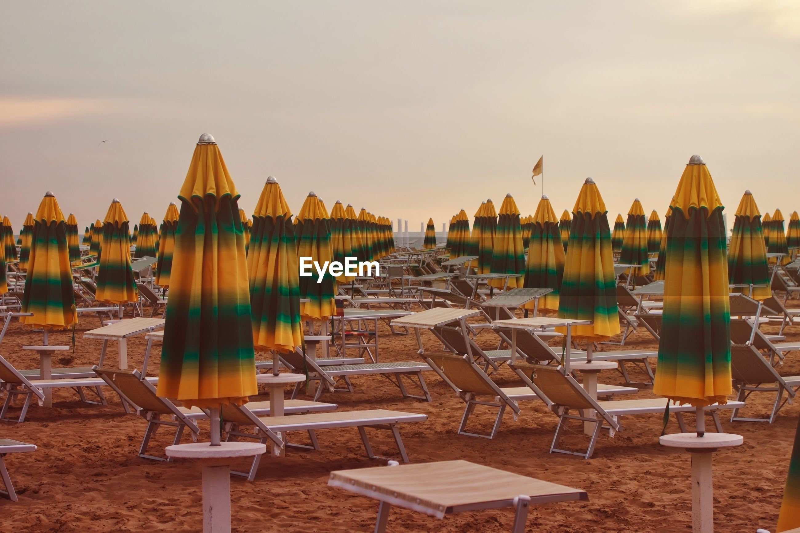Empty chairs and umbrellas on  beach against sky