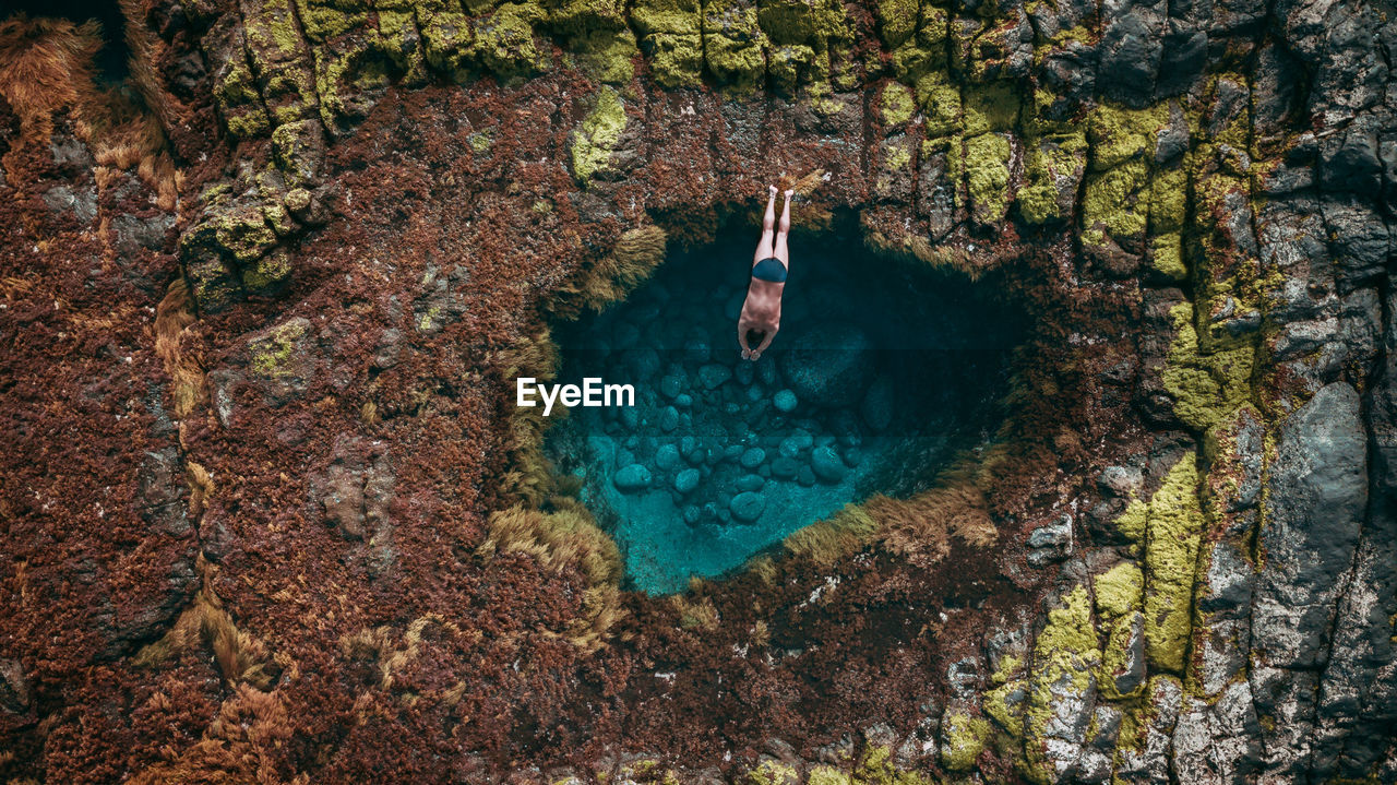 High angle view of shirtless man diving in sea against sky