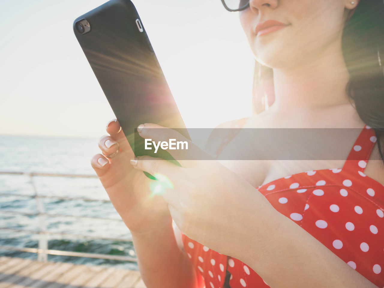Midsection Of Woman Using Mobile Phone By Sea During Sunny Day