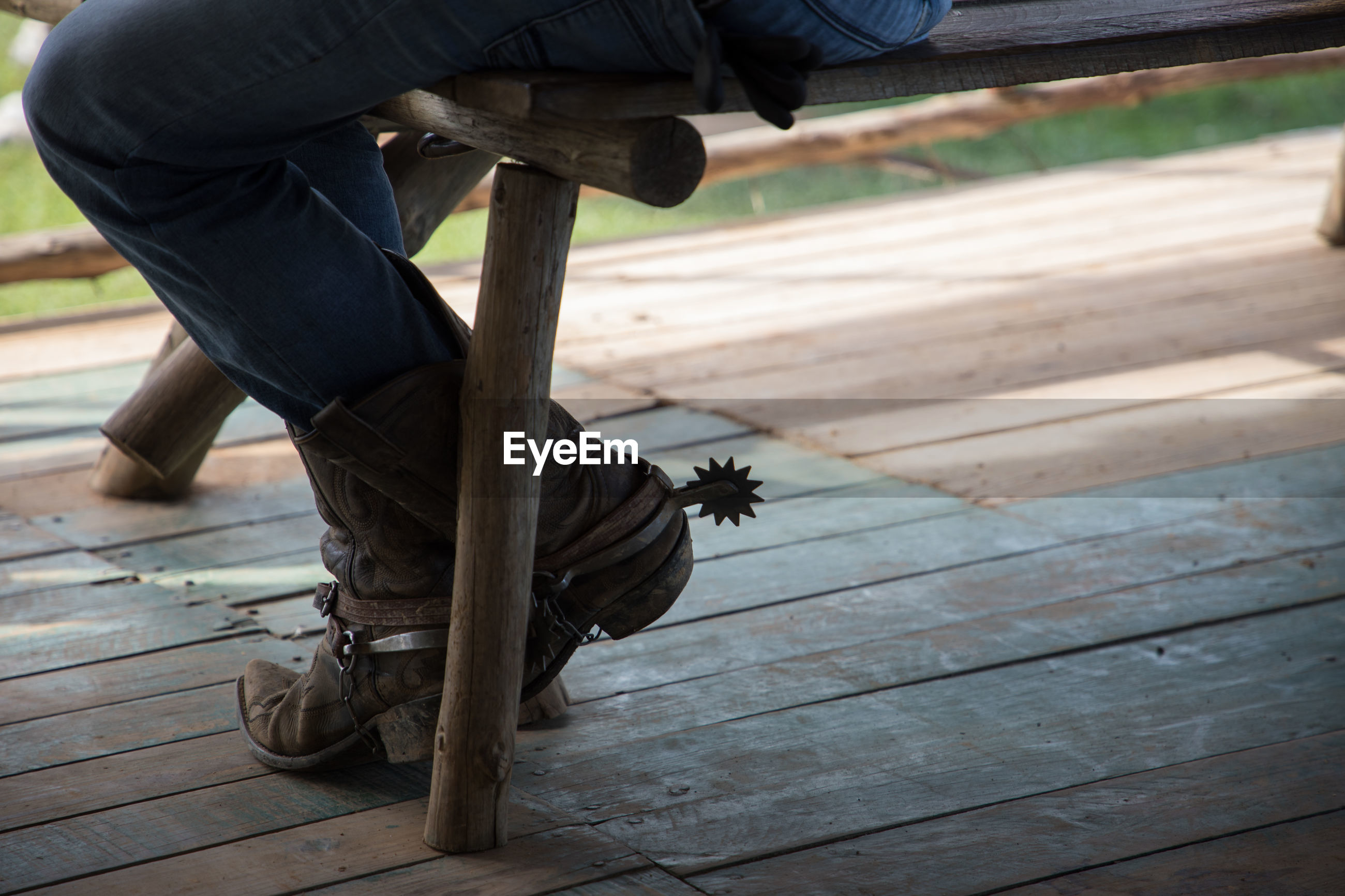 Low section of man wearing boots sitting on bench