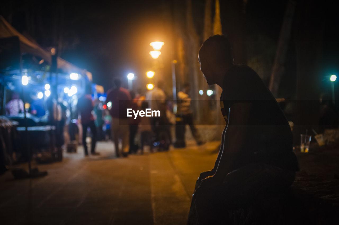 Man Sitting At Night Street Market