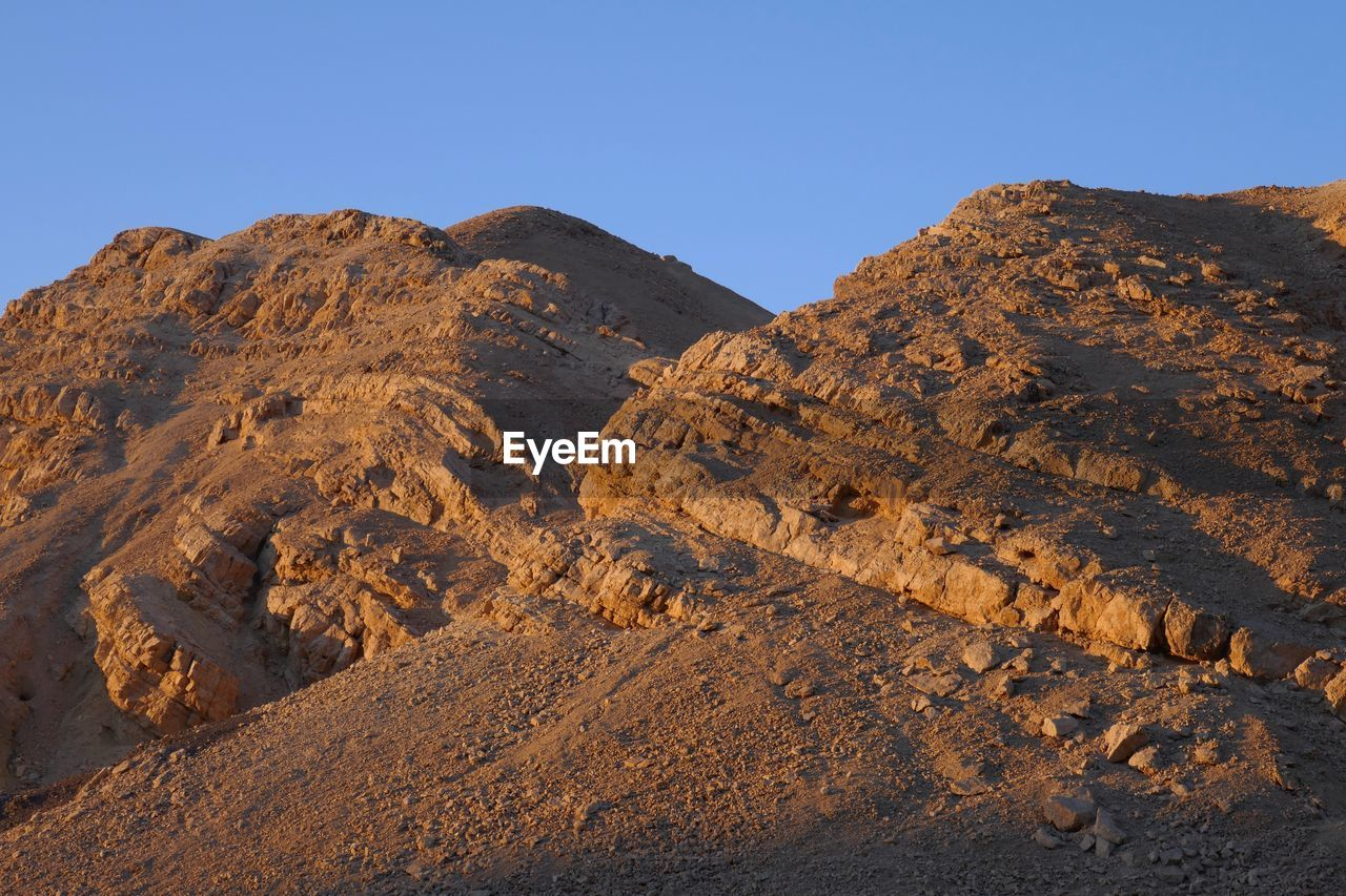 sky, mountain, scenics - nature, nature, clear sky, rock, beauty in nature, no people, tranquil scene, mountain range, environment, tranquility, geology, land, landscape, physical geography, rock - object, non-urban scene, rock formation, solid, climate, formation, arid climate, outdoors, mountain peak, eroded