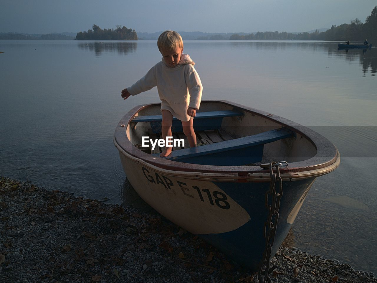 BOY STANDING IN BOAT ON LAKE