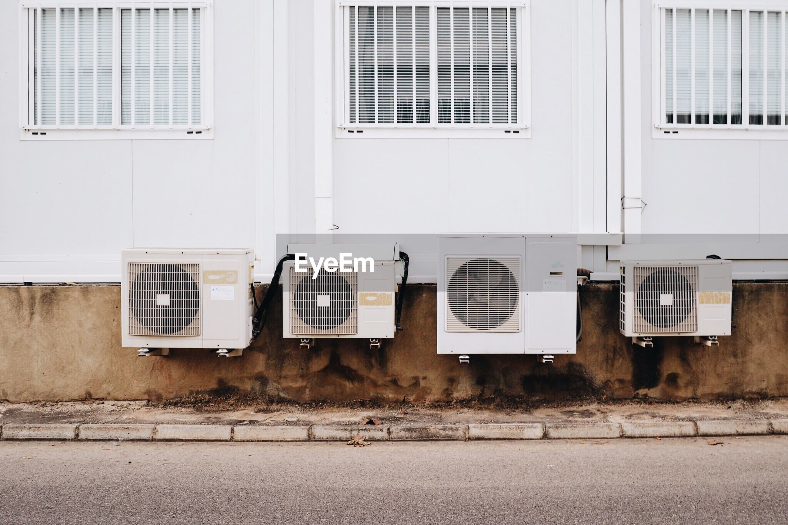 Air conditioners mounted on building by sidewalk