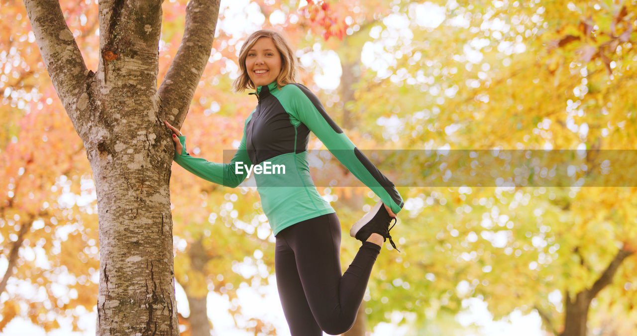 Young Woman Stretching Leg While Exercising By Tree Trunk In Park During Autumn