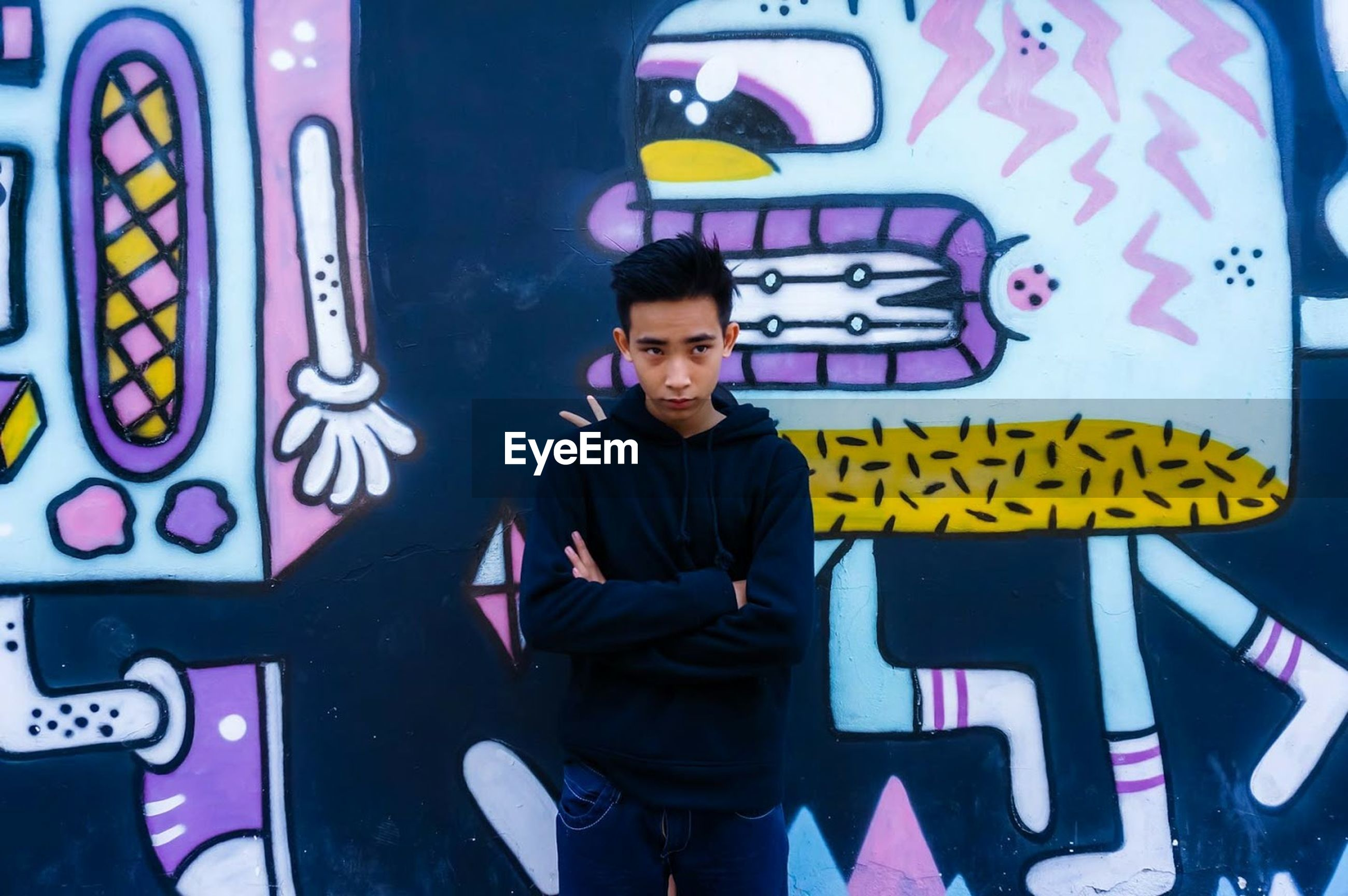 lifestyles, casual clothing, leisure activity, looking at camera, standing, front view, portrait, text, person, art, graffiti, young adult, creativity, communication, three quarter length, young men, art and craft, waist up