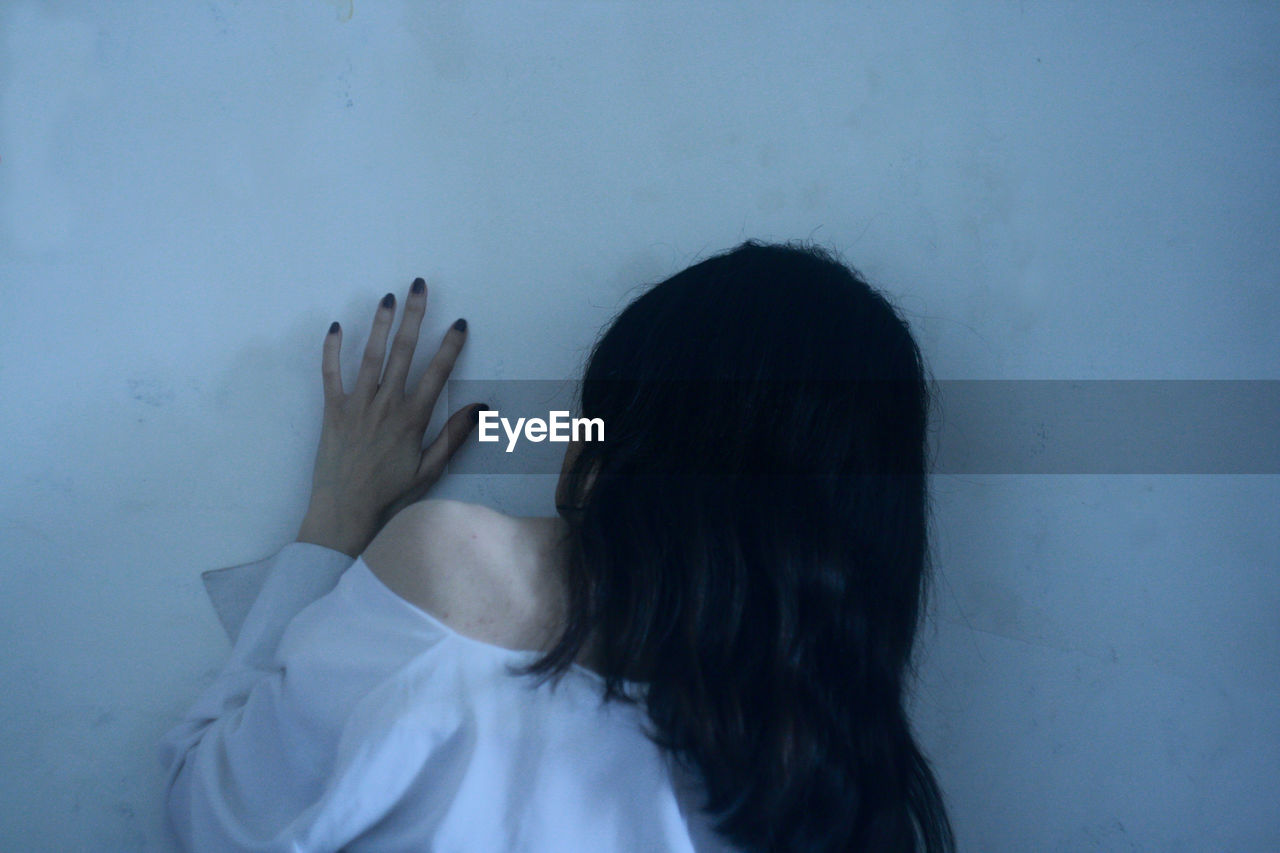 Rear View Of Woman Touching Wall