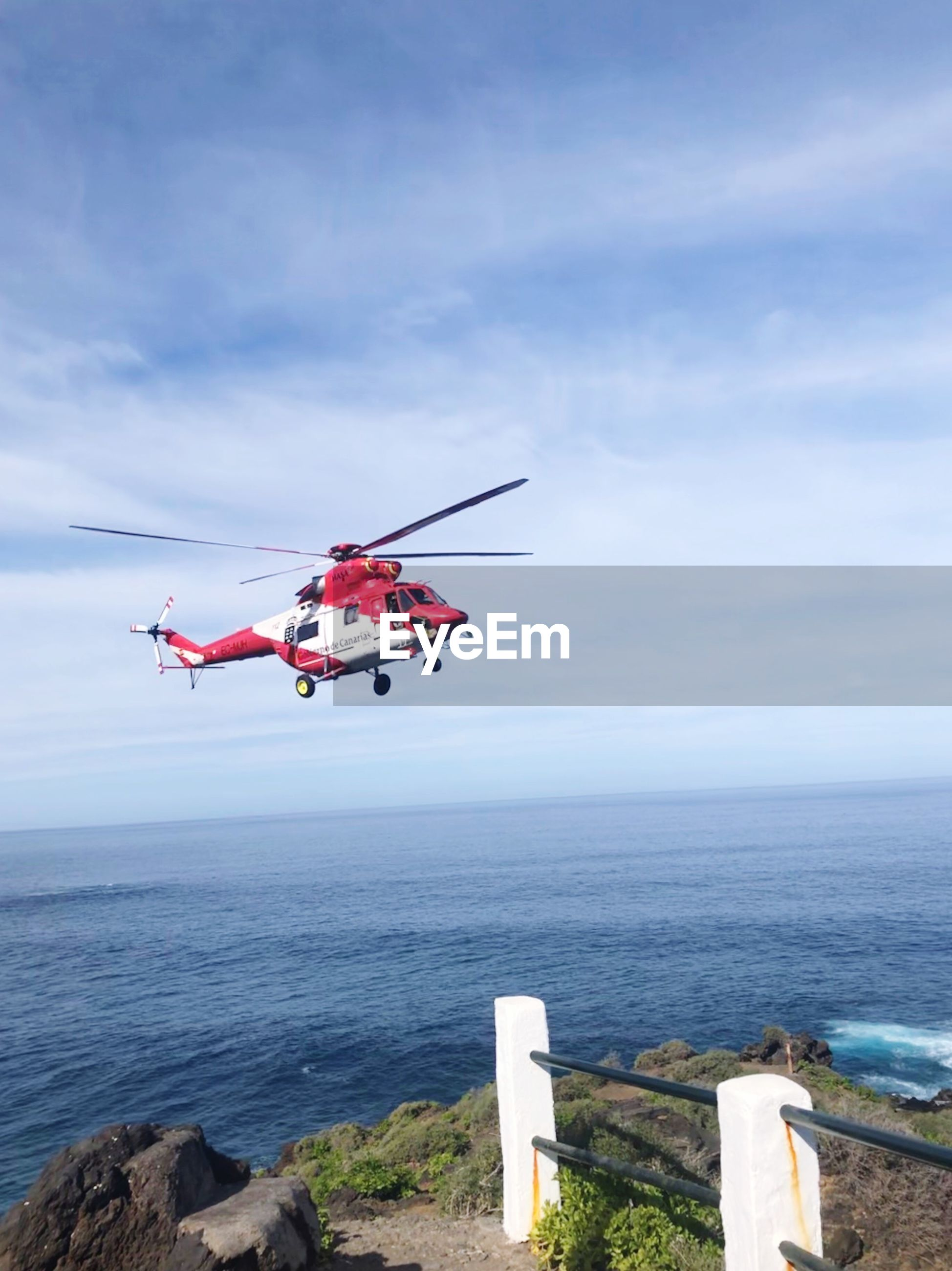LOW ANGLE VIEW OF HELICOPTER FLYING OVER SEA