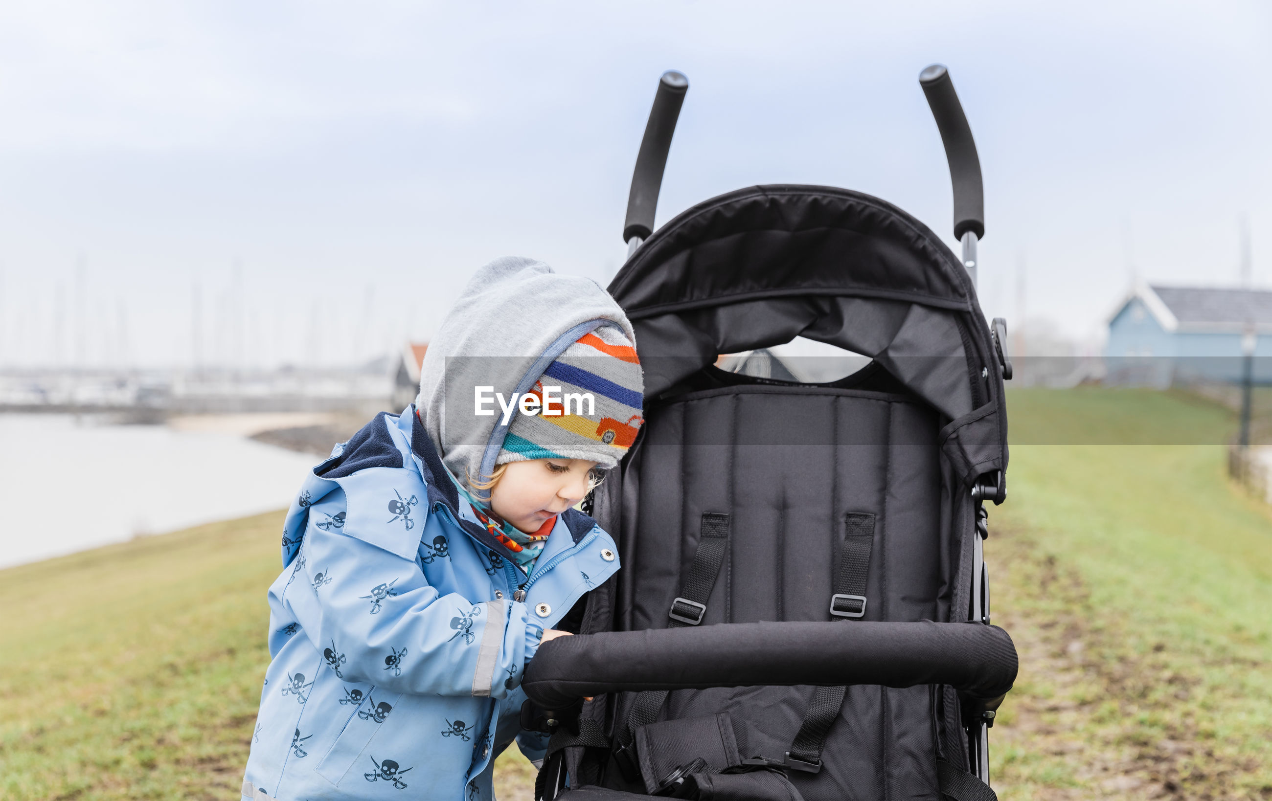 Girl wearing warm clothing looking at baby stroller on field