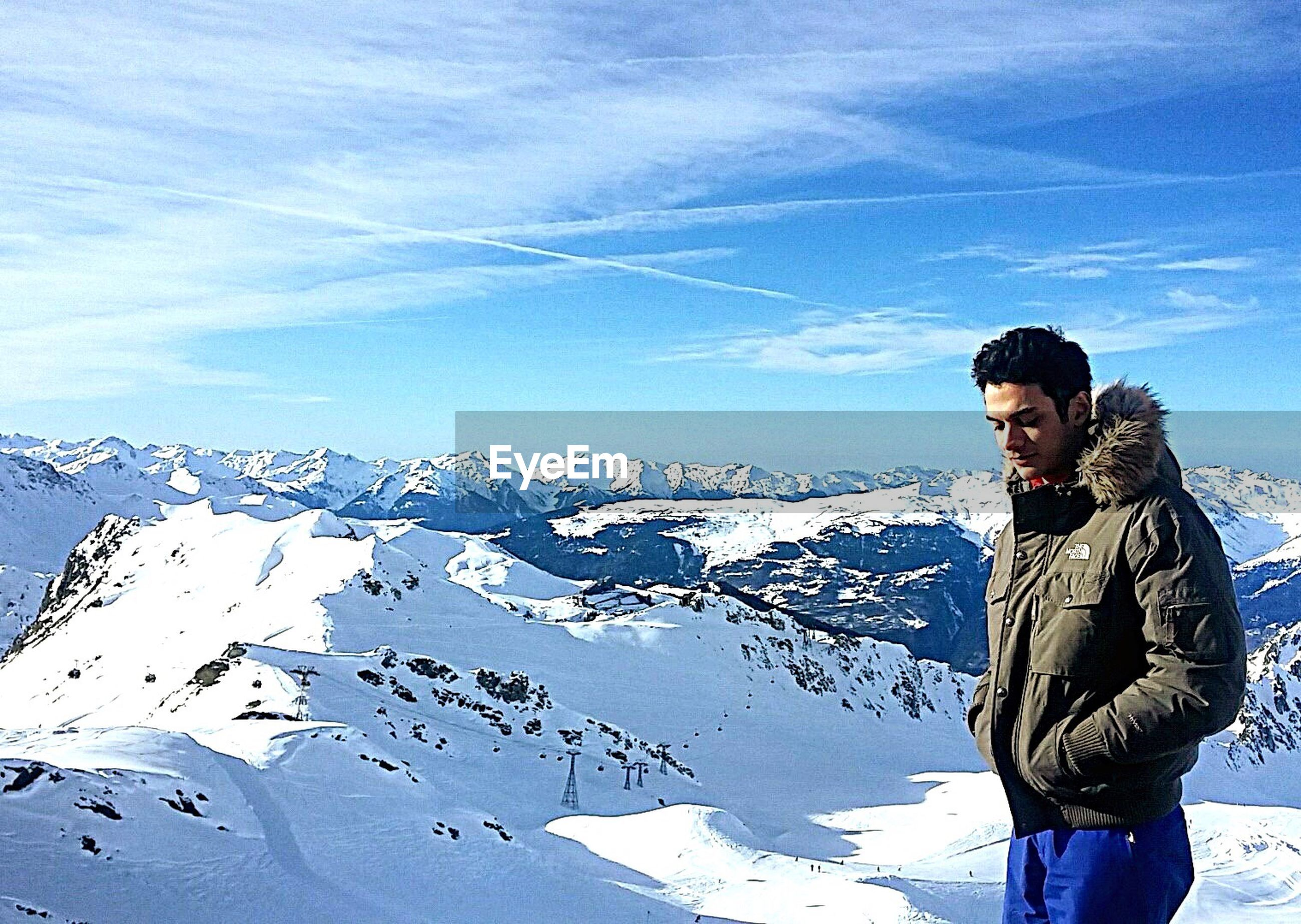 winter, lifestyles, snow, leisure activity, cold temperature, mountain, young adult, warm clothing, casual clothing, standing, sky, full length, person, landscape, season, tranquil scene, mountain range, tranquility