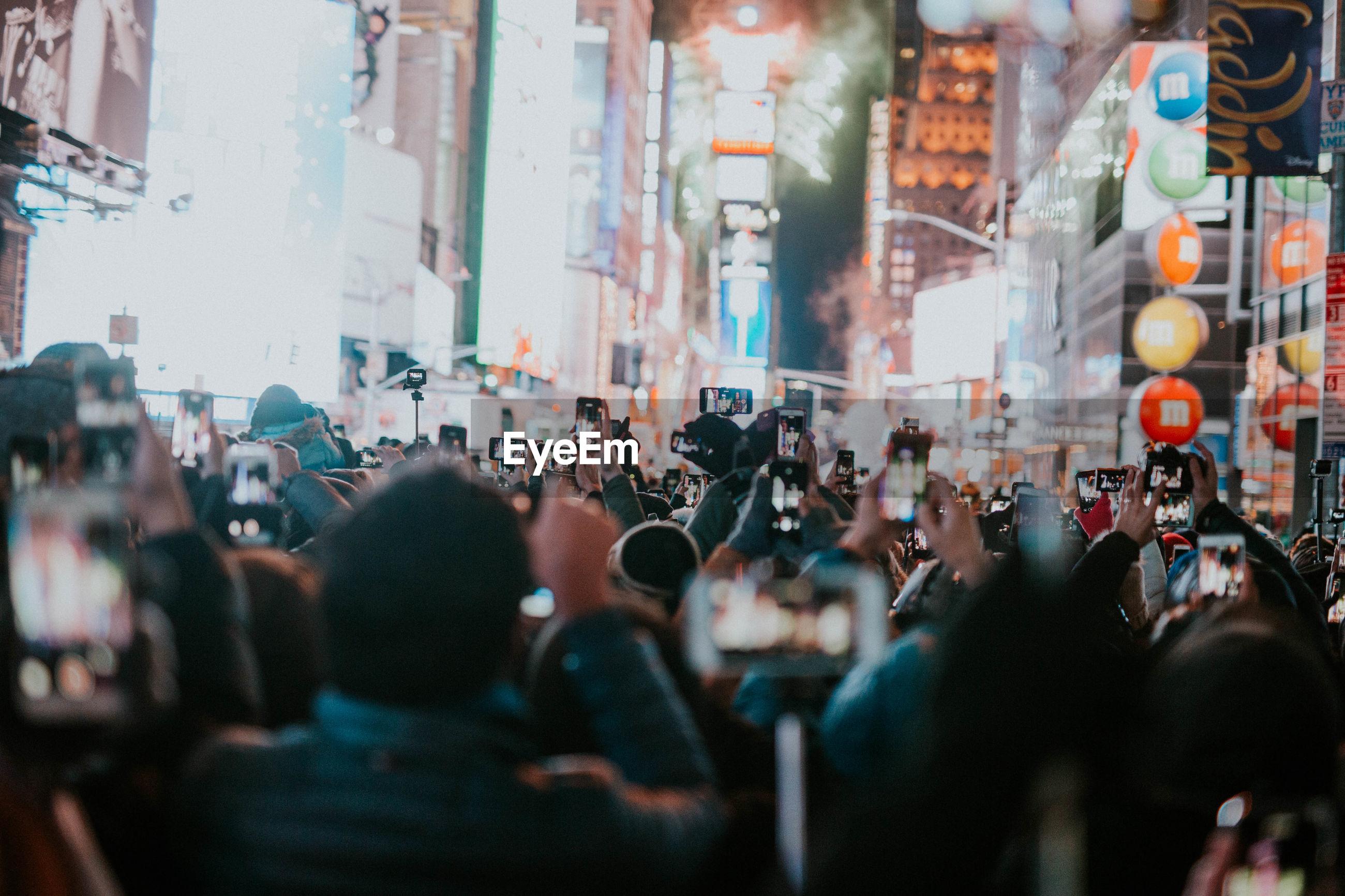 Crowd photographing on illuminated street at night