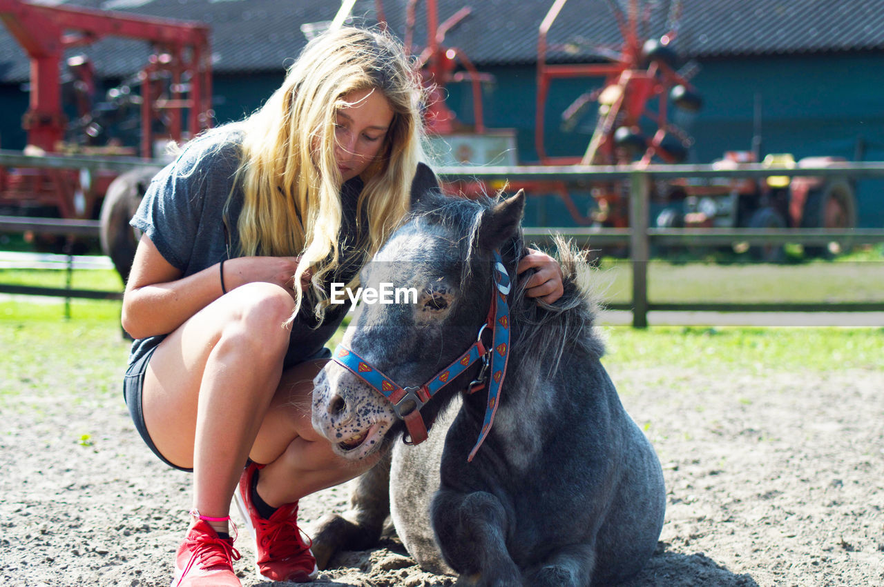 Rear view of woman petting pony
