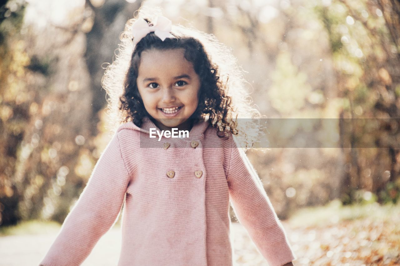 Portrait of cute girl standing against trees