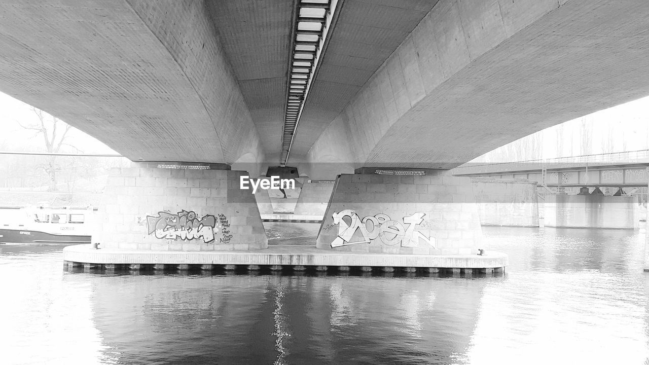 architecture, built structure, transportation, water, bridge, connection, bridge - man made structure, river, no people, reflection, below, waterfront, nature, underneath, day, architectural column, city, indoors, ceiling