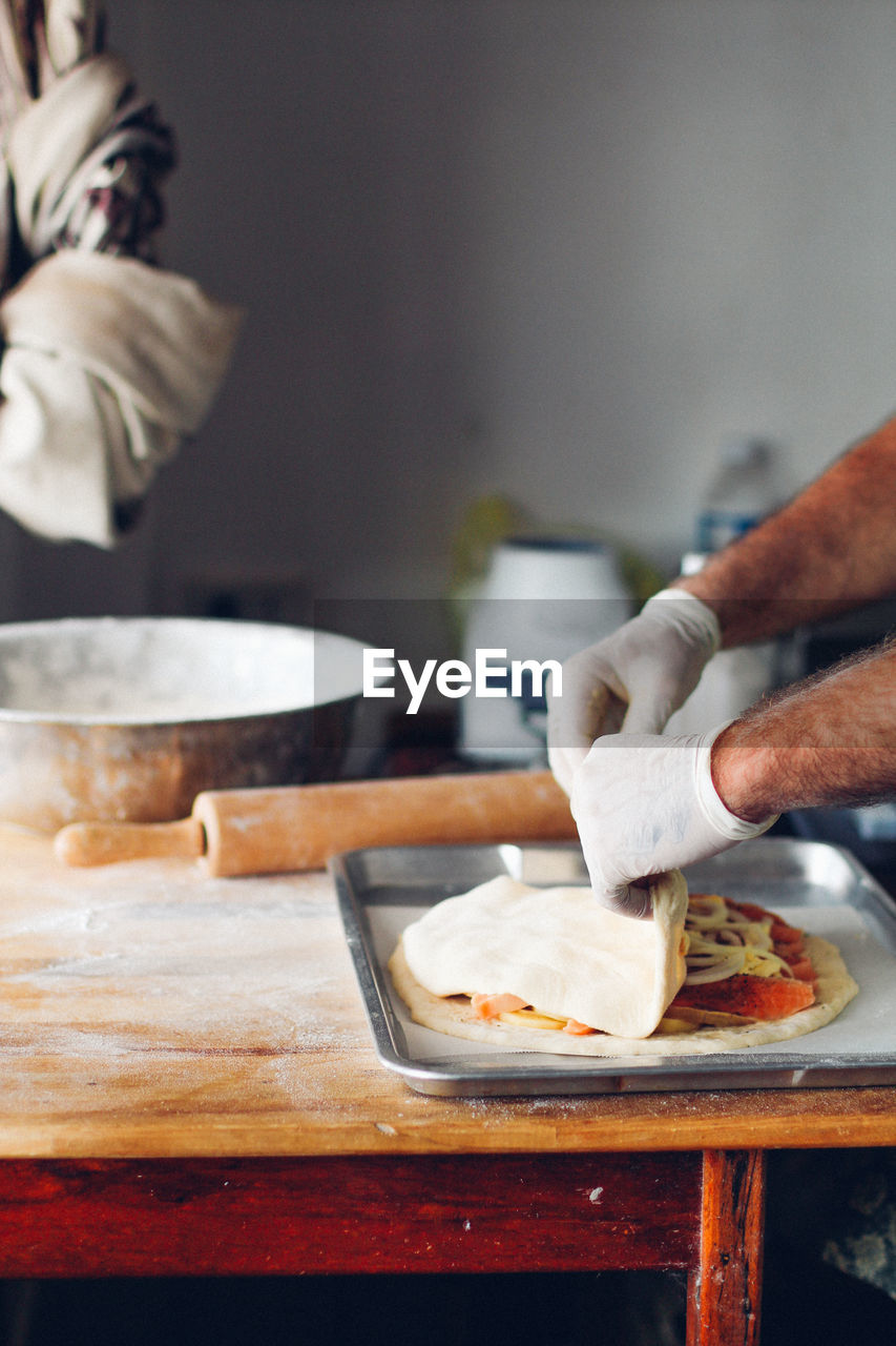 Cropped Hands Of Man Preparing Food In Kitchen