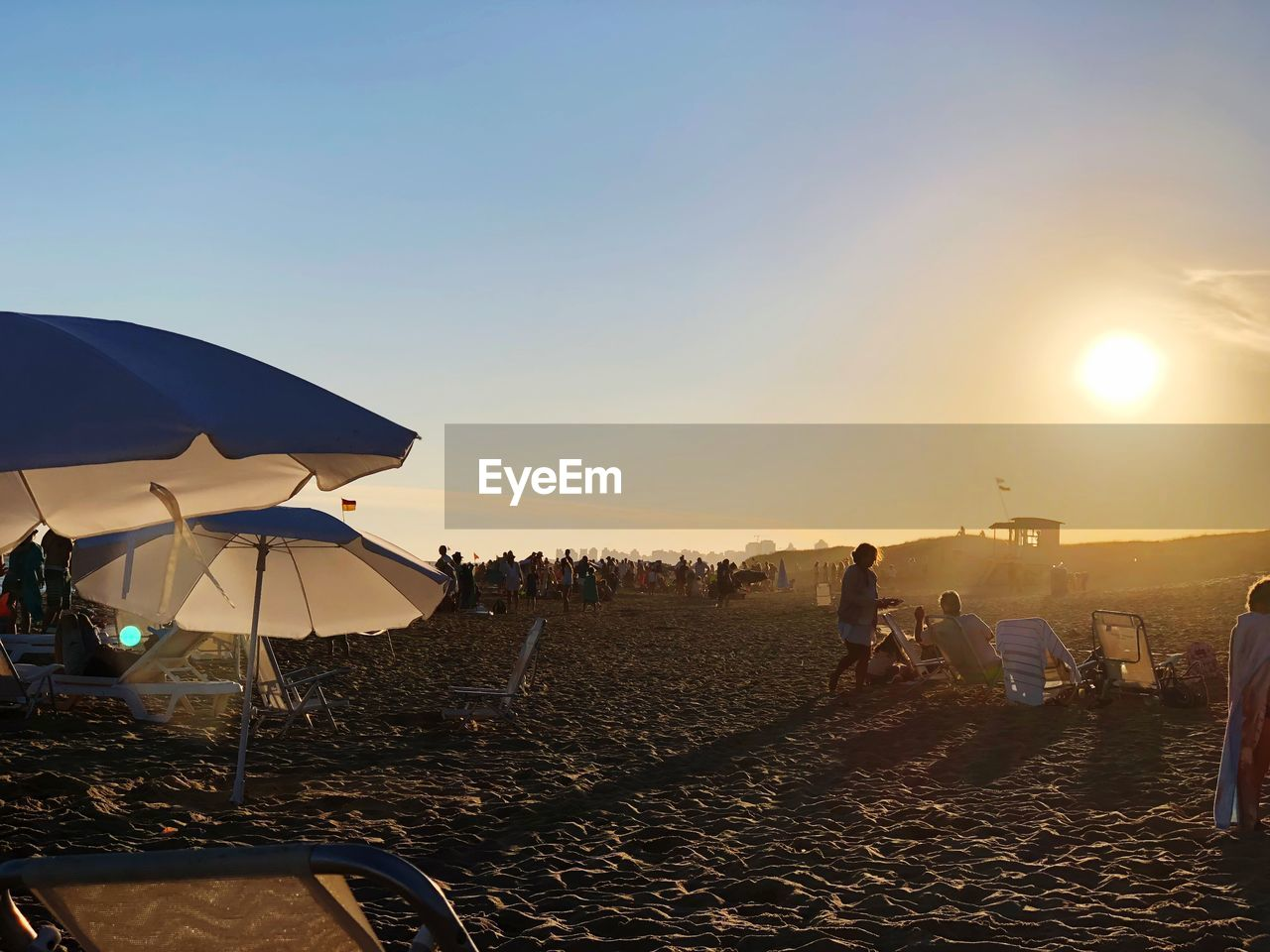 sky, land, umbrella, beach, parasol, nature, protection, sunset, real people, sand, sun, clear sky, sunlight, lifestyles, leisure activity, beach umbrella, large group of people, crowd, security, group of people, lens flare, outdoors