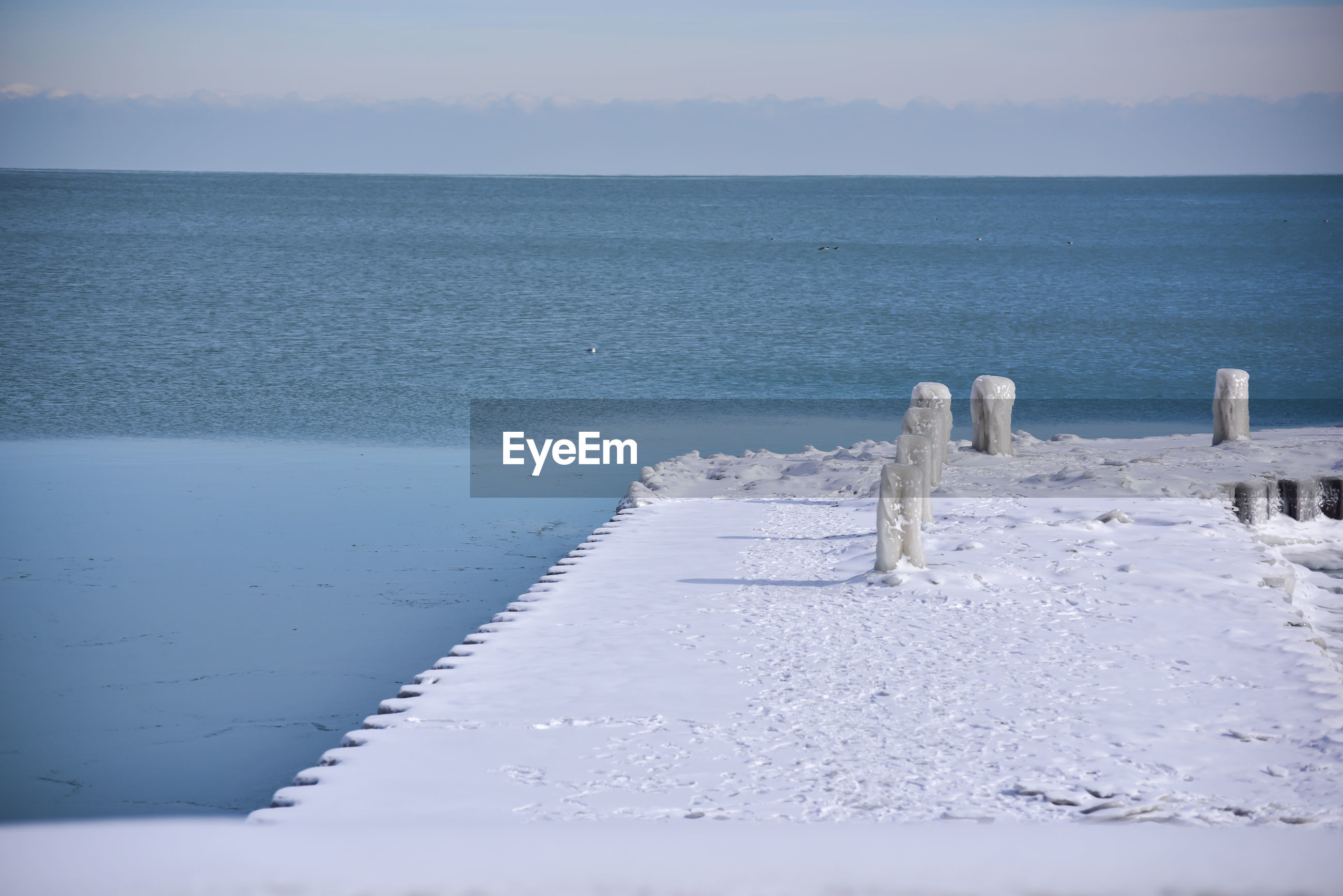 WOODEN POSTS ON FROZEN SEA AGAINST SKY DURING WINTER