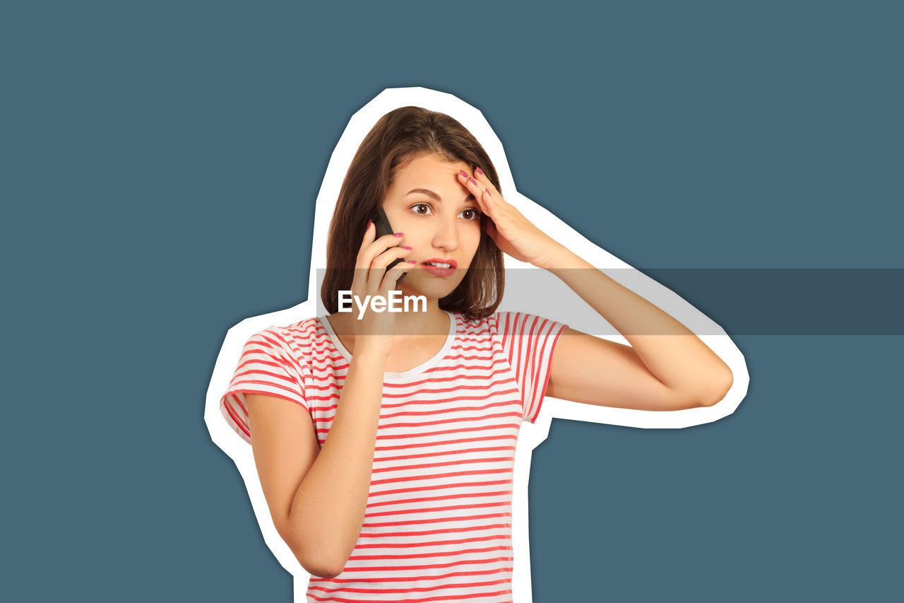 Young woman talking over mobile phone against gray background