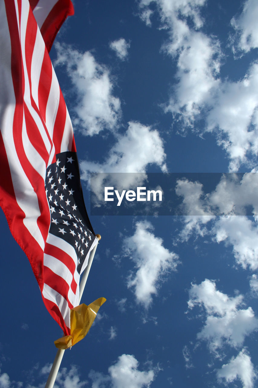 sky, cloud - sky, low angle view, flag, striped, nature, patriotism, day, blue, no people, star shape, outdoors, red, wind, environment, sunlight, white color, national icon, independence