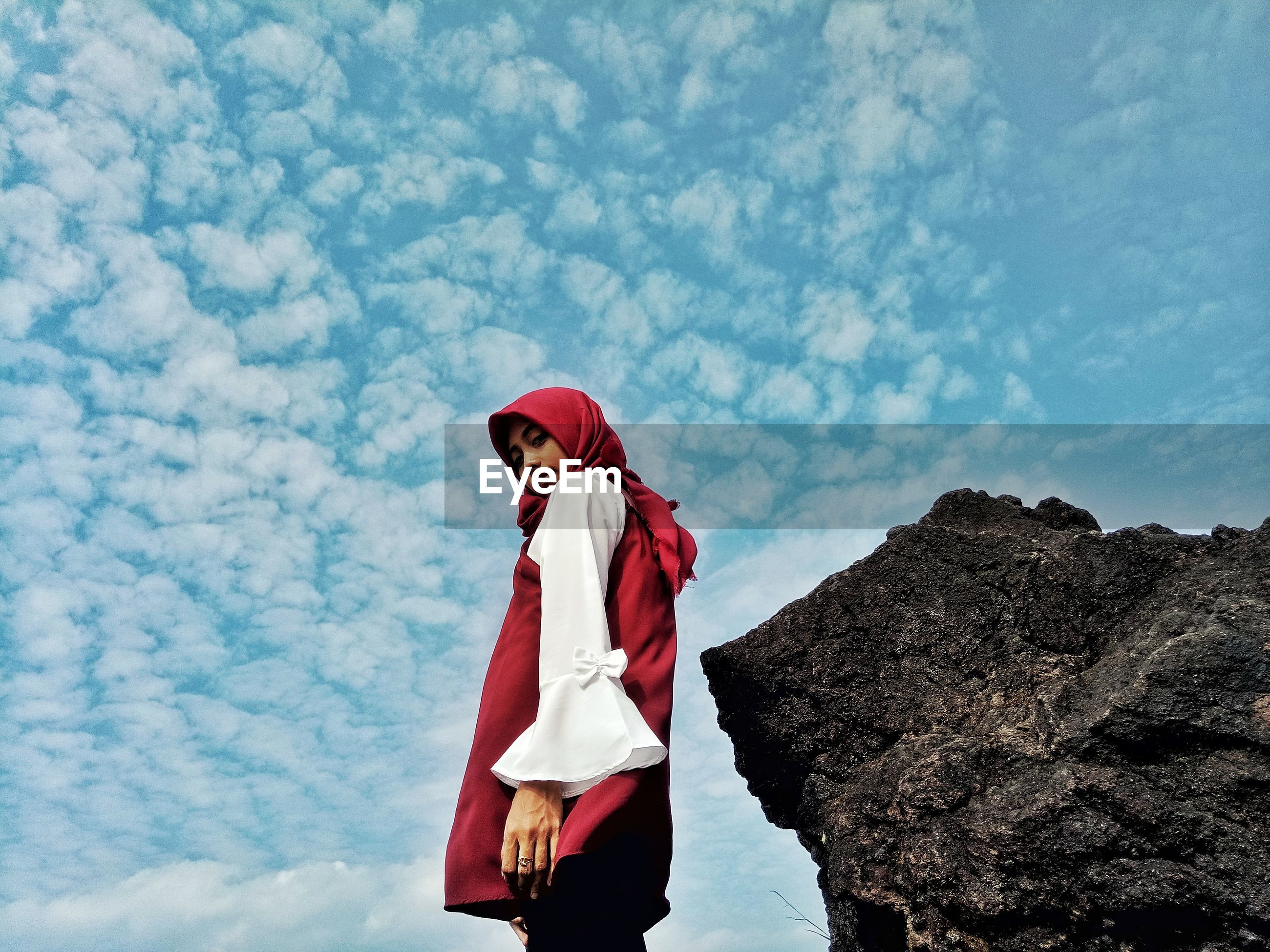 Low angle portrait of girl wearing hijab standing by rock against cloudy sky