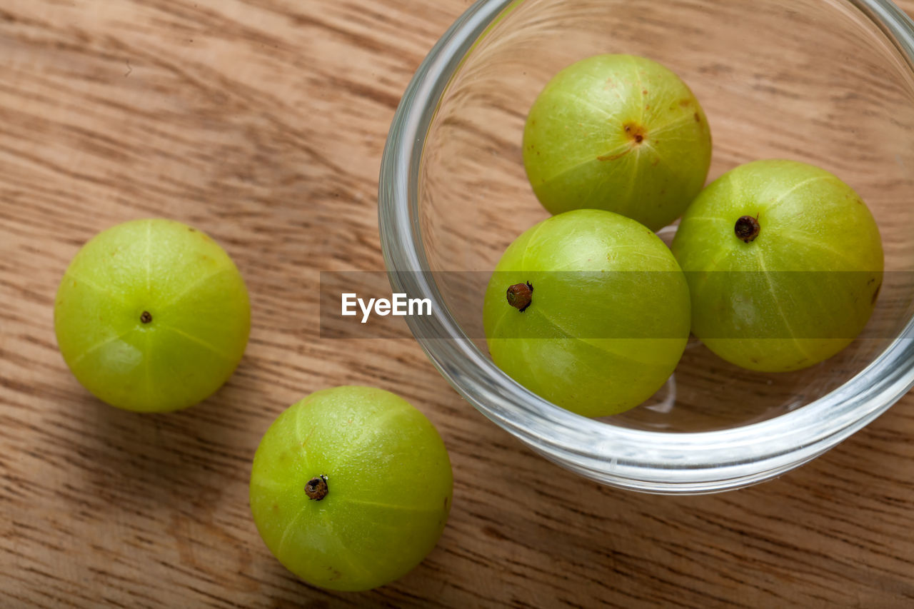 food, healthy eating, food and drink, fruit, freshness, wellbeing, green color, still life, table, wood - material, apple - fruit, indoors, high angle view, close-up, no people, apple, granny smith apple, container, pear, group of objects