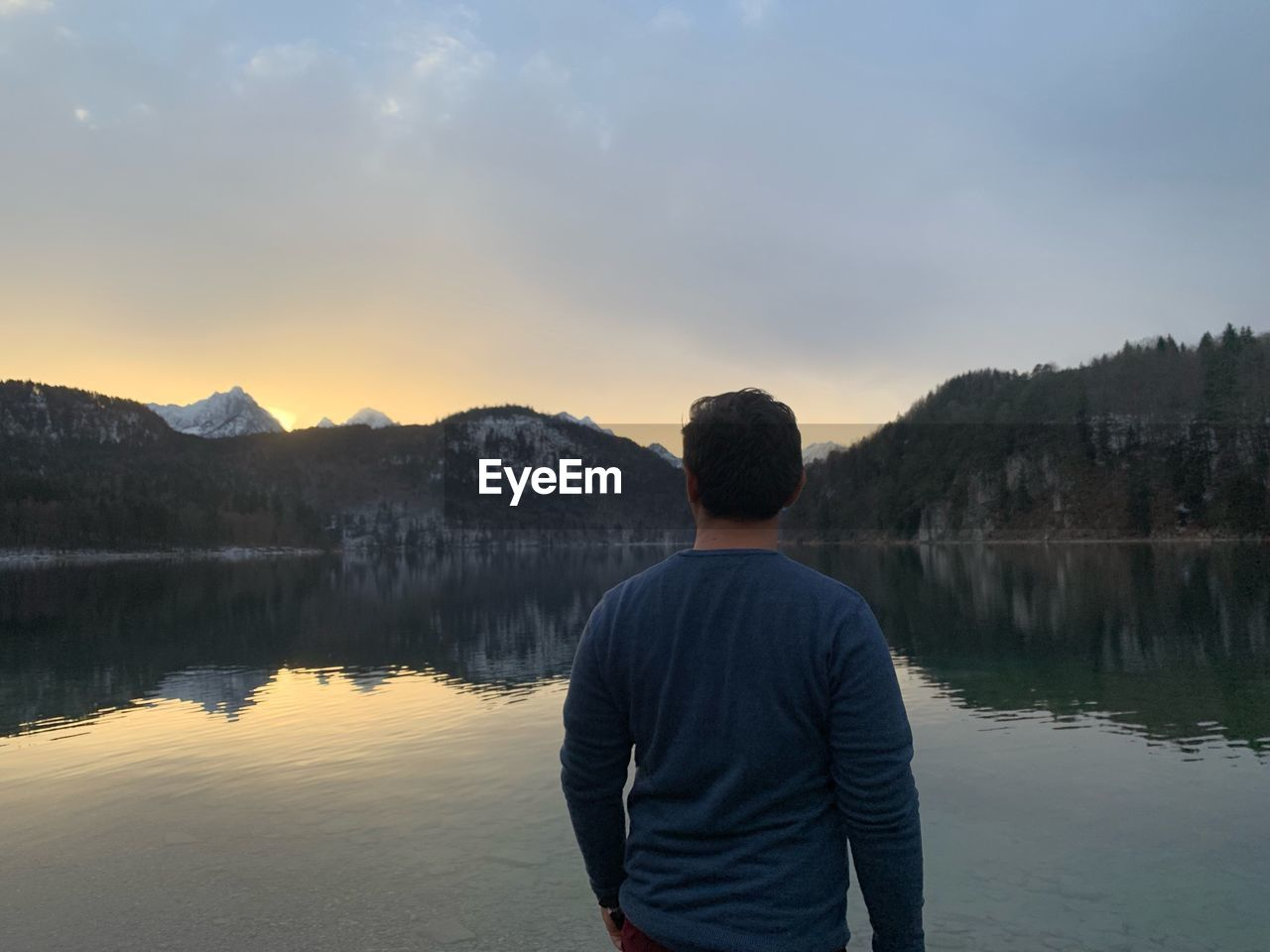 Rear view of man looking at lake against cloudy sky during sunset