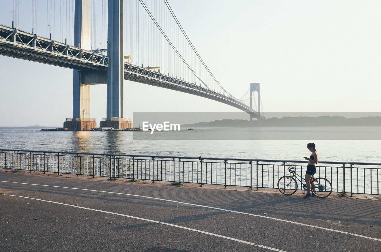 Side View Of Woman With Bicycle Using Smart Phone While Standing On Promenade Against Sky During Sunset