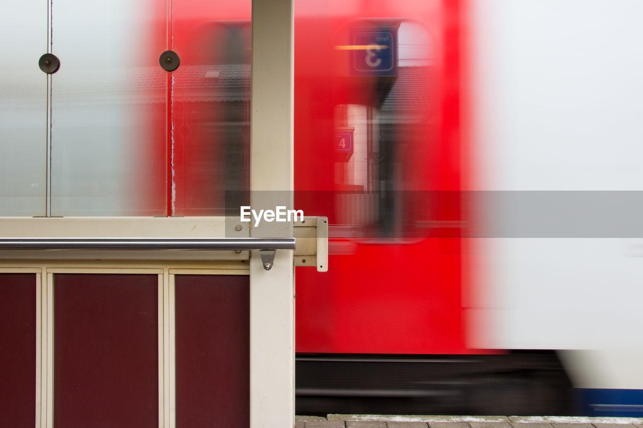 Blurred motion of red train at railroad station platform