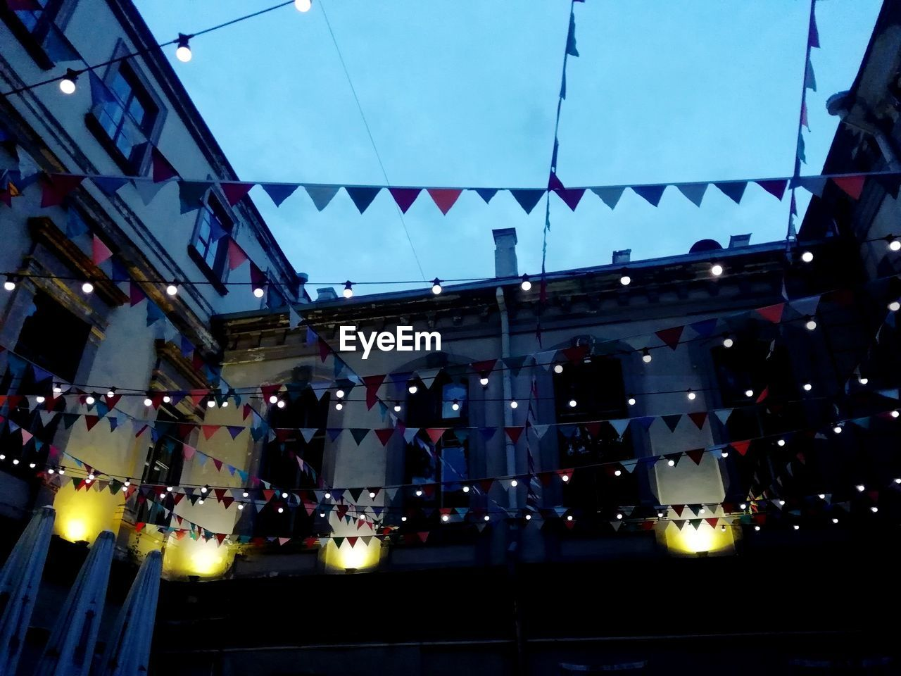 decoration, illuminated, built structure, hanging, architecture, building exterior, low angle view, lighting equipment, celebration, bunting, no people, building, flag, sky, nature, event, outdoors, dusk, night, ceiling