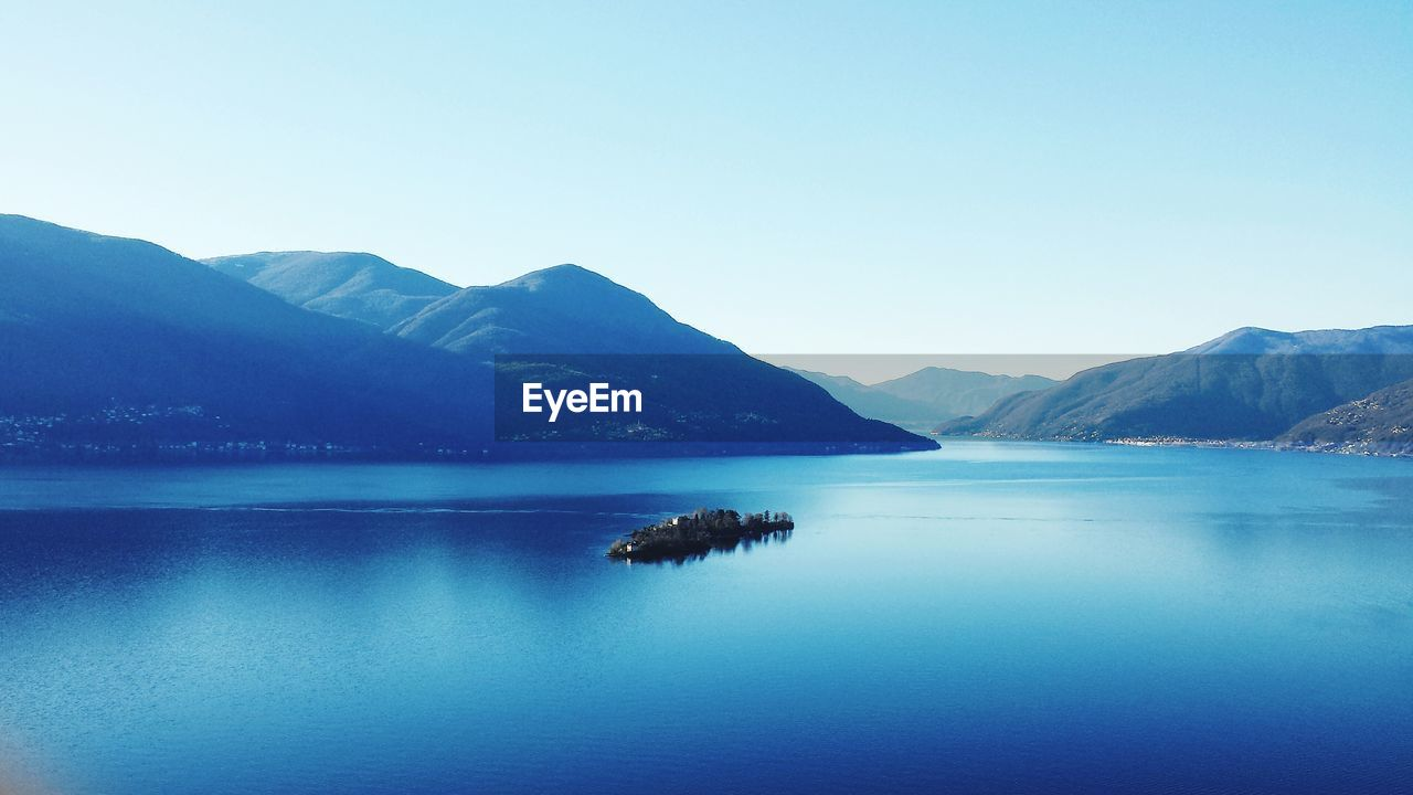 mountain, tranquil scene, tranquility, beauty in nature, scenics, nature, water, mountain range, idyllic, lake, copy space, blue, clear sky, no people, remote, outdoors, waterfront, day, sky