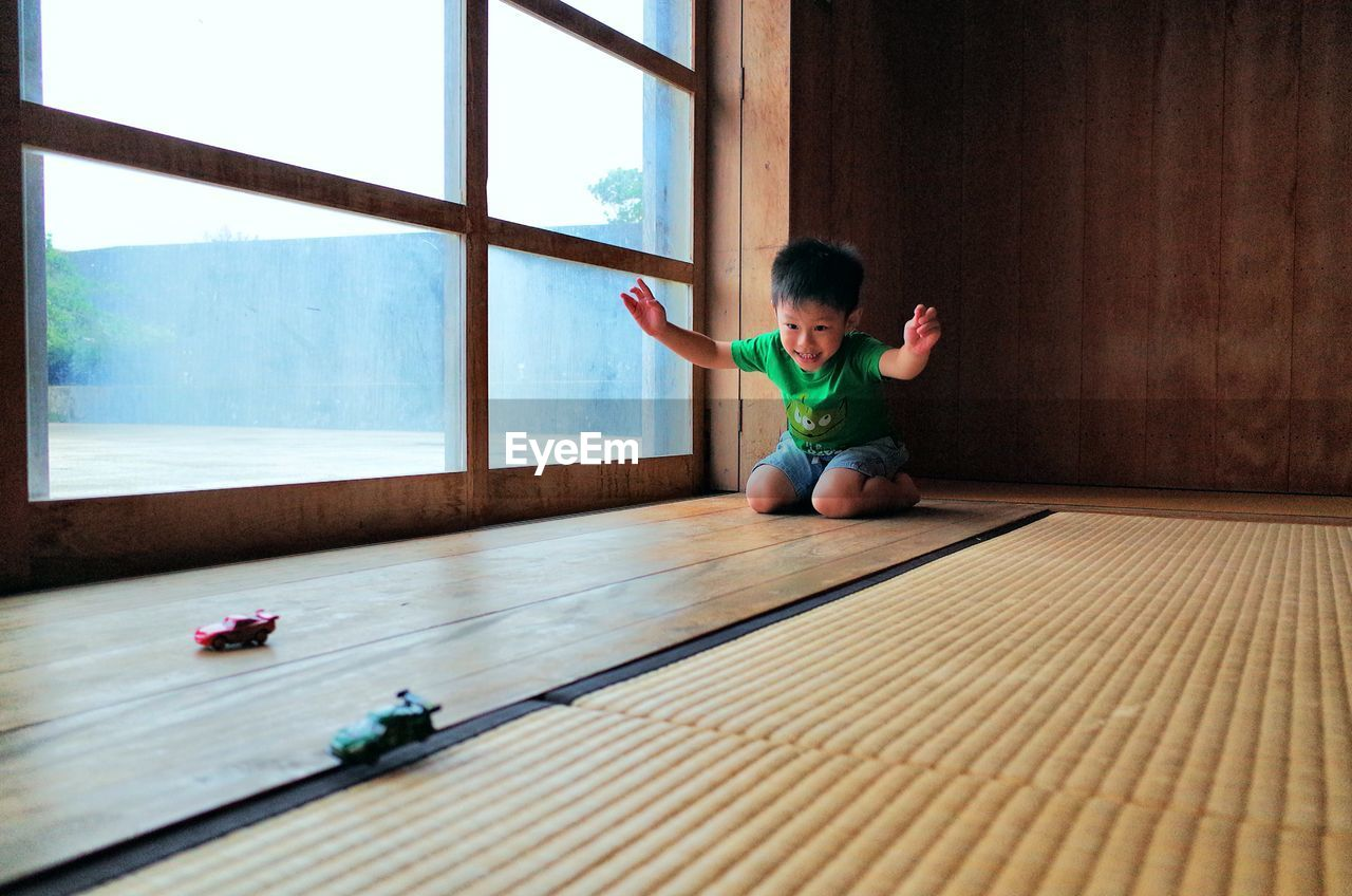 full length, one person, indoors, real people, childhood, lifestyles, child, wood, sport, leisure activity, casual clothing, flooring, boys, hardwood floor, window, front view, home interior, emotion, human arm, arms raised, innocence