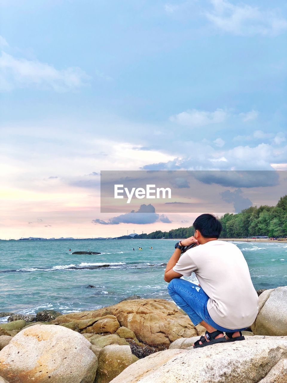 water, real people, one person, rock, sea, rock - object, solid, leisure activity, lifestyles, sky, beauty in nature, scenics - nature, sitting, casual clothing, rear view, cloud - sky, land, non-urban scene, outdoors, looking at view, horizon over water