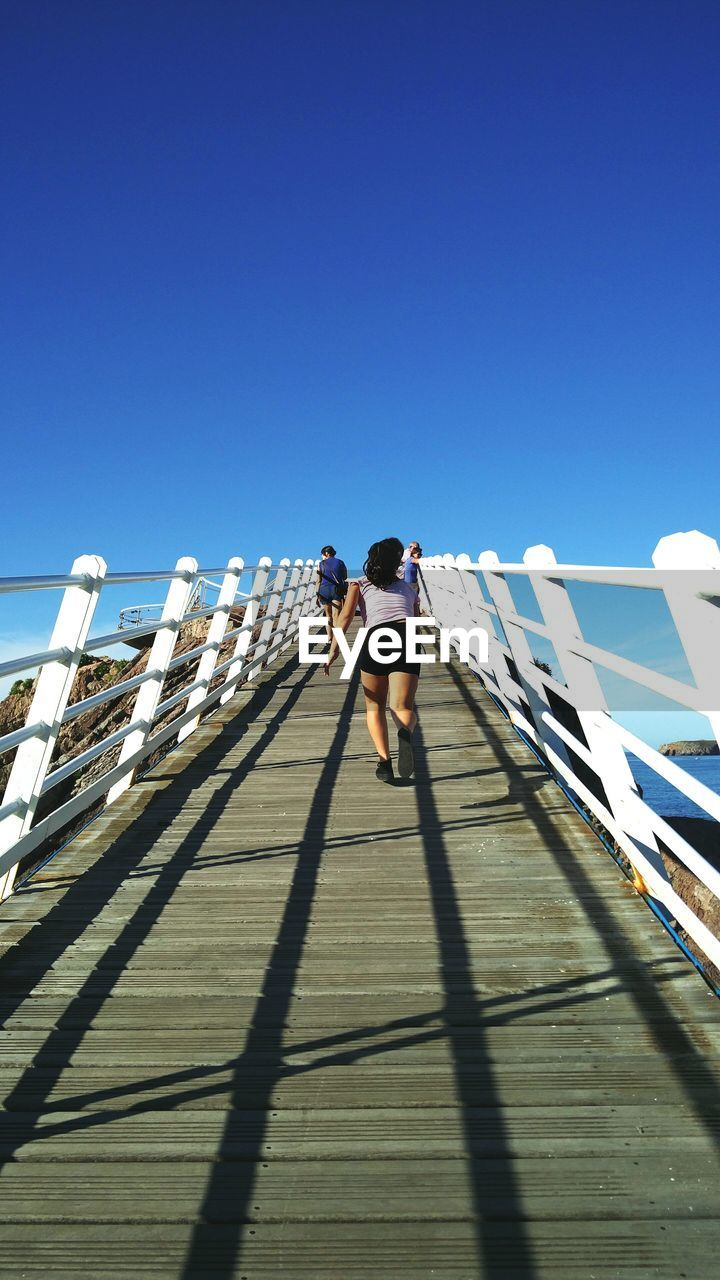sunlight, shadow, clear sky, copy space, day, walking, full length, real people, lifestyles, men, outdoors, architecture, one person, sky, people