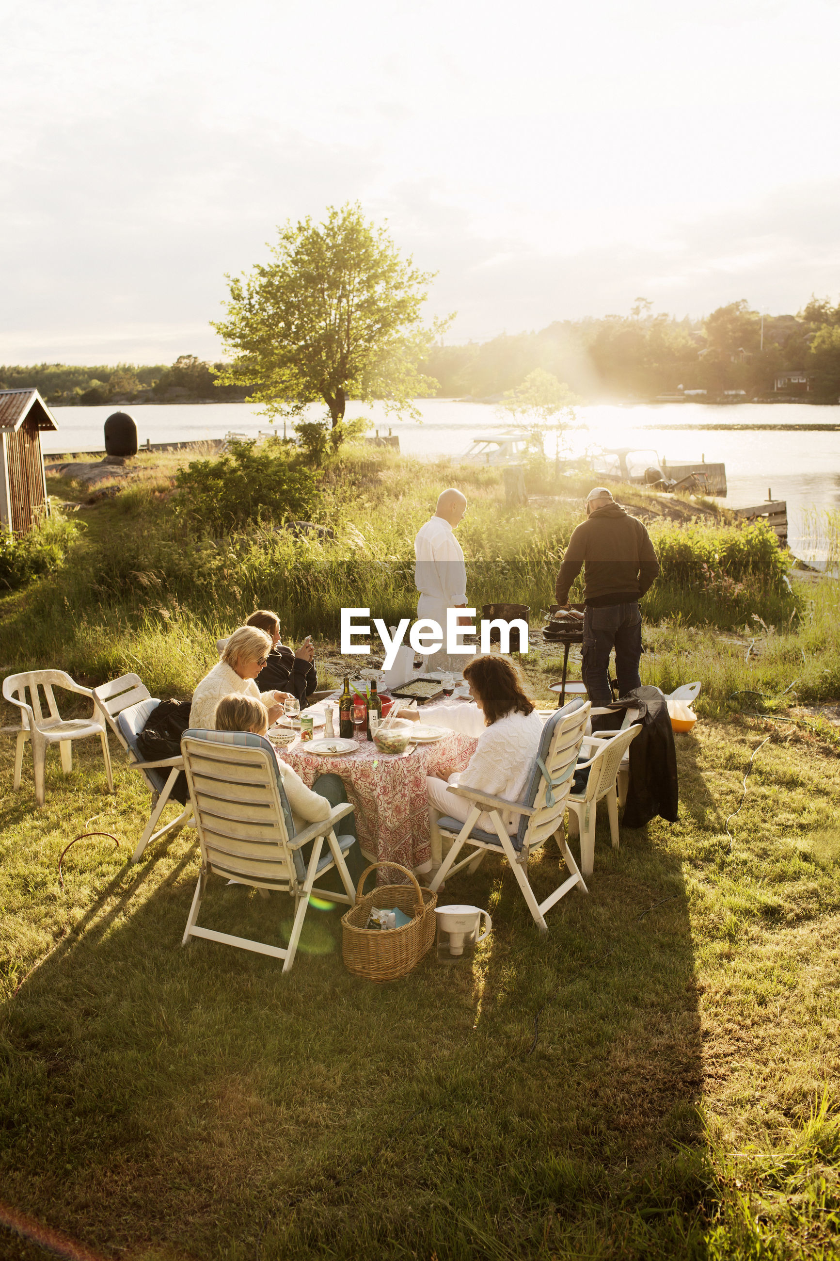 GROUP OF PEOPLE SITTING ON TABLE AT FARM