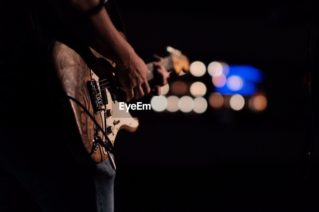 Midsection Of Person Playing Guitar At Night