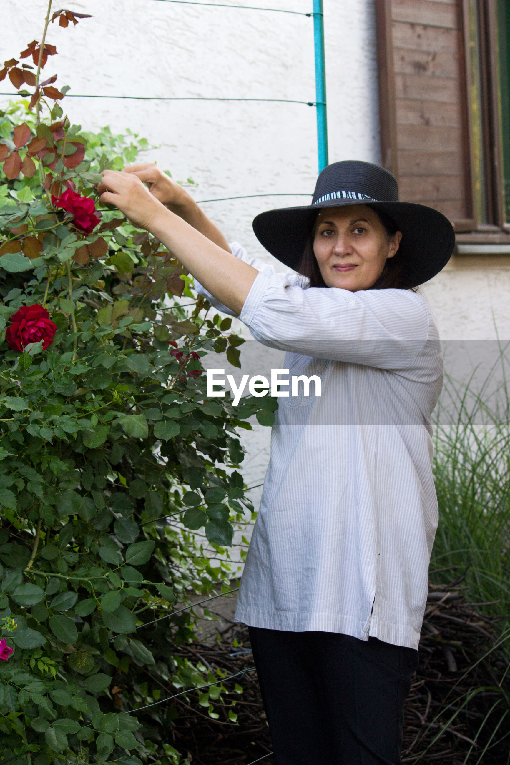Portrait of smiling woman cutting while standing by plants