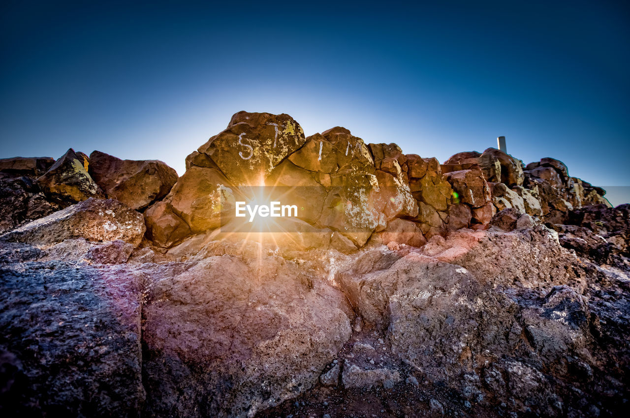 rock - object, rock formation, geology, tranquility, nature, tranquil scene, beauty in nature, sunlight, physical geography, scenics, blue, no people, sky, outdoors, mountain, clear sky, landscape, day