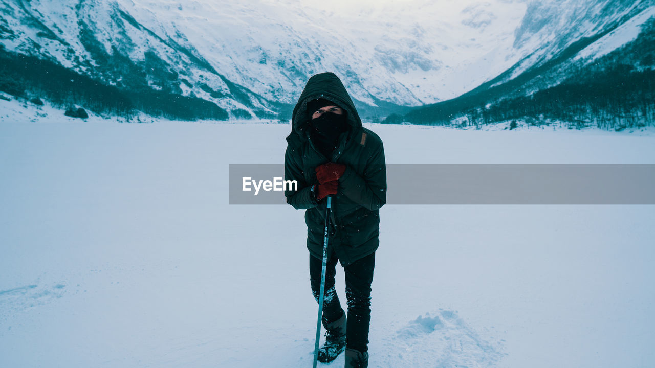 Full length portrait of man standing on snow covered land against mountains