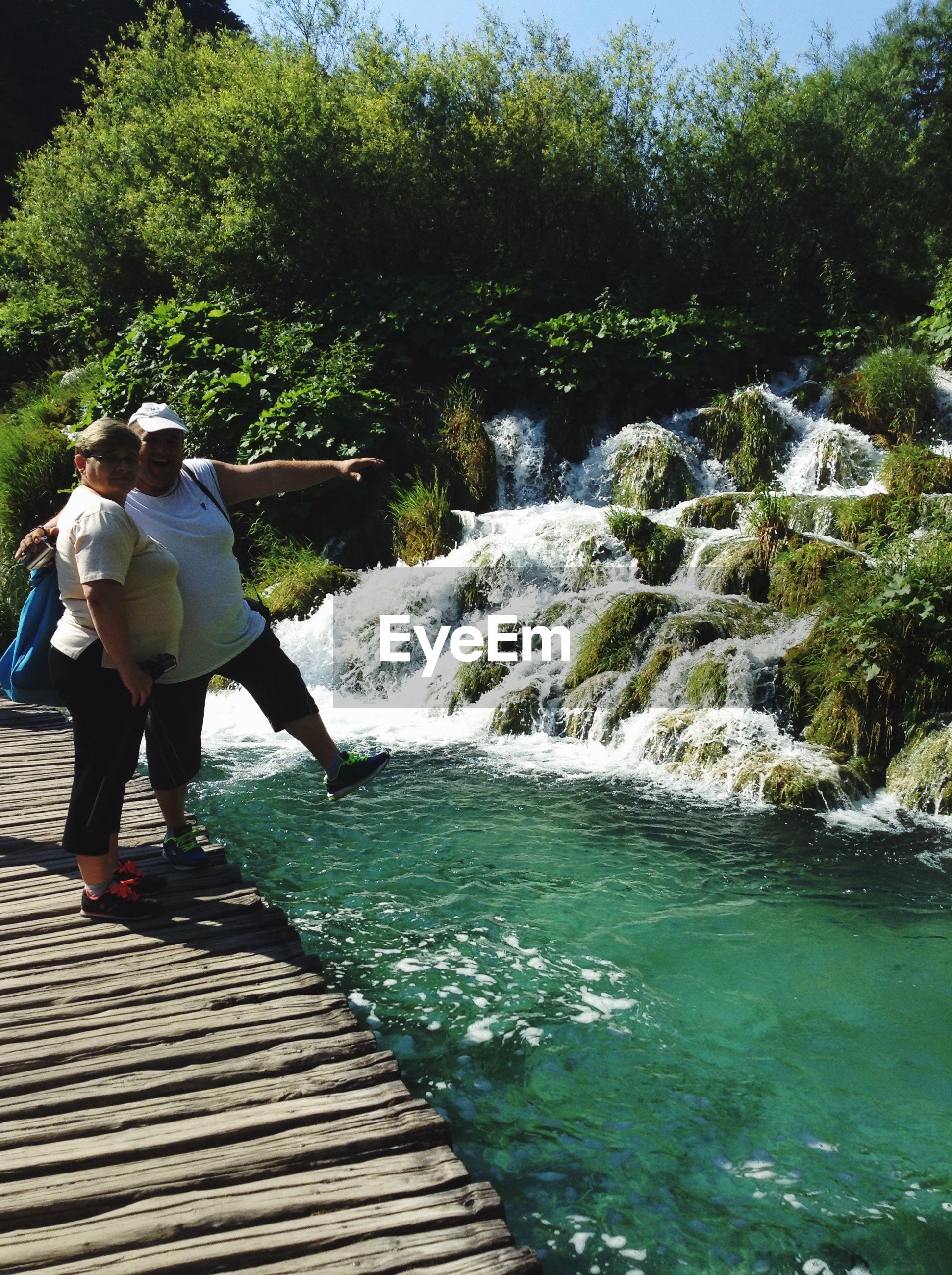 water, lifestyles, leisure activity, full length, motion, tree, waterfall, flowing water, rear view, men, casual clothing, river, nature, standing, flowing, rock - object, forest, splashing