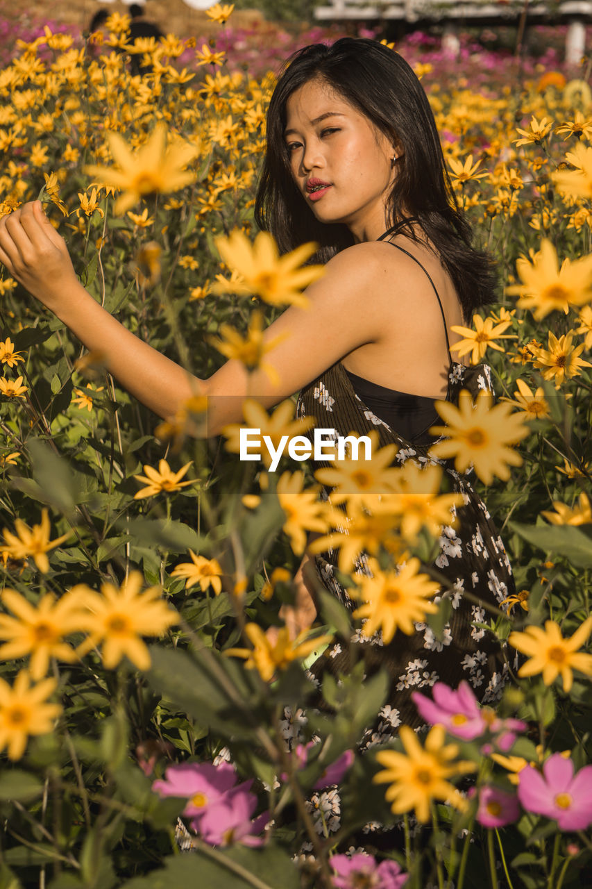 Portrait of woman by yellow blooming flowers
