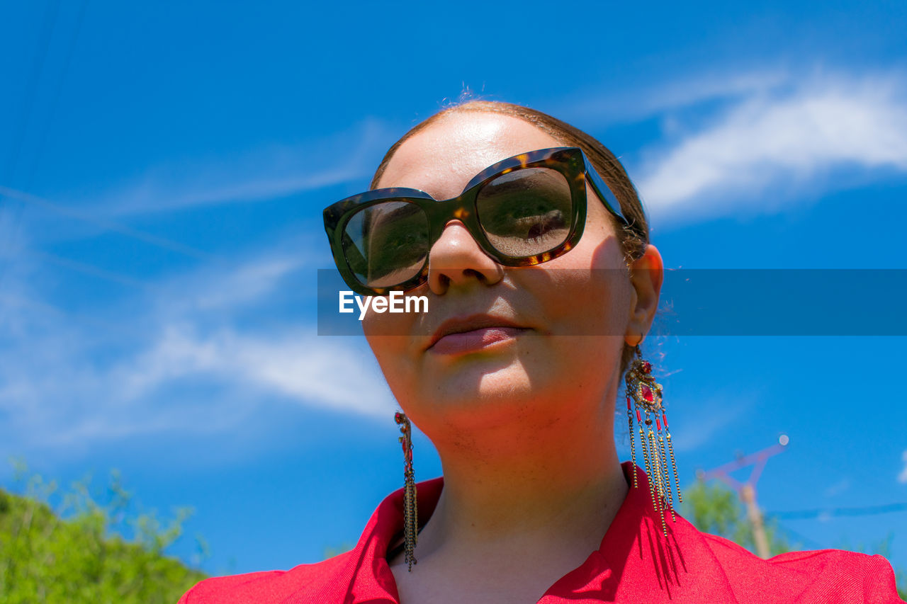 Low angle view of woman wearing sunglasses against blue sky